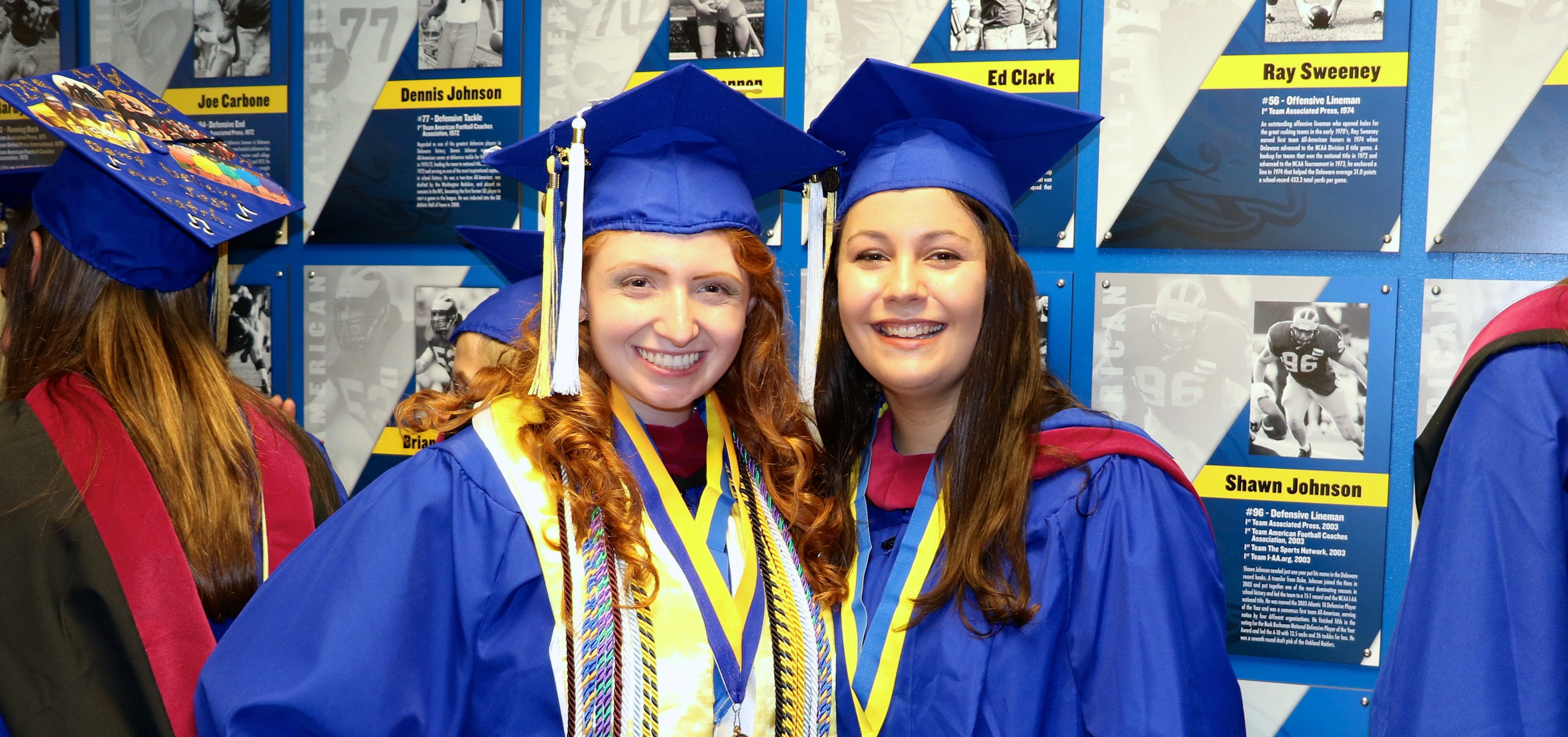 Two College of Education and Human Development students wait in line before graduation ceremonies.