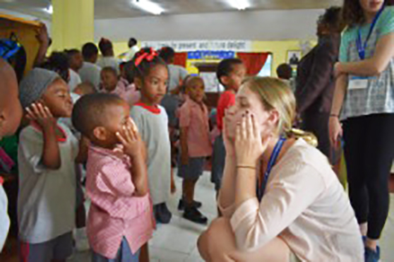 UD student teacher with children in Barbados