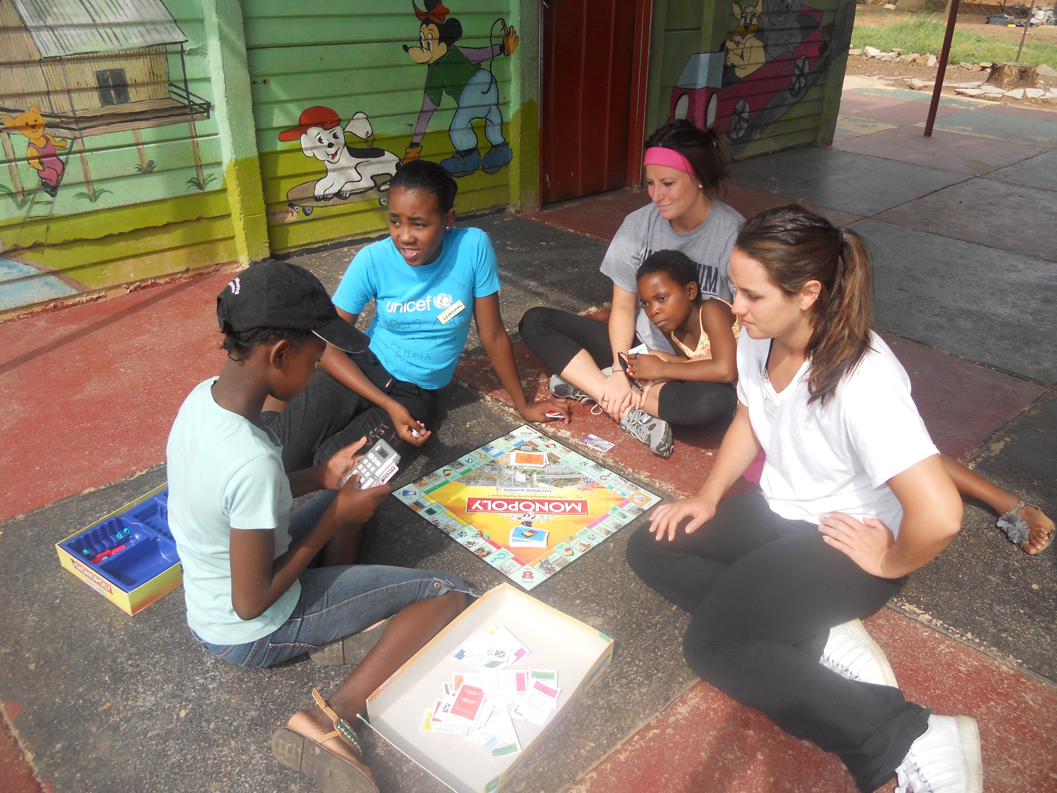 UD student teacher playing Monopoly with children at South African day care
