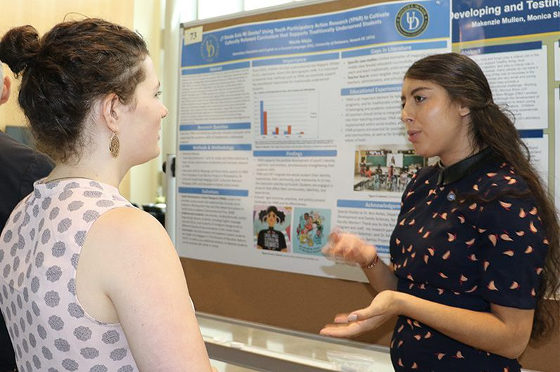 Nicole Mejia speaks to a woman next to her Summer Scholars research poster