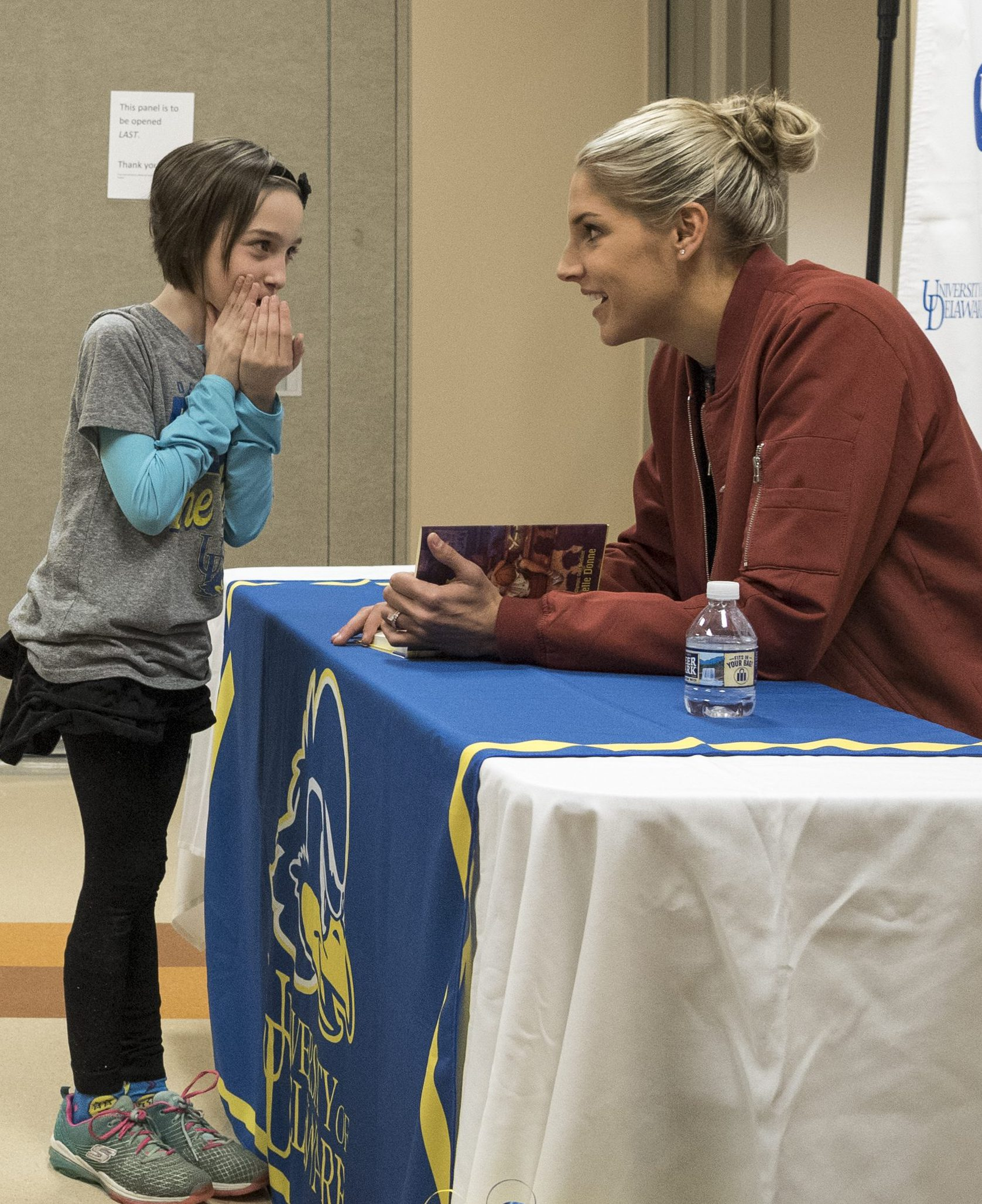 Child shares a secret with Elena Delle Donne at The College School book signing