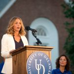 Nikki Dombrowski speaks at the 2016 Twilight Induction Ceremony. She is standing at a podium with the University of Delaware logo on it.