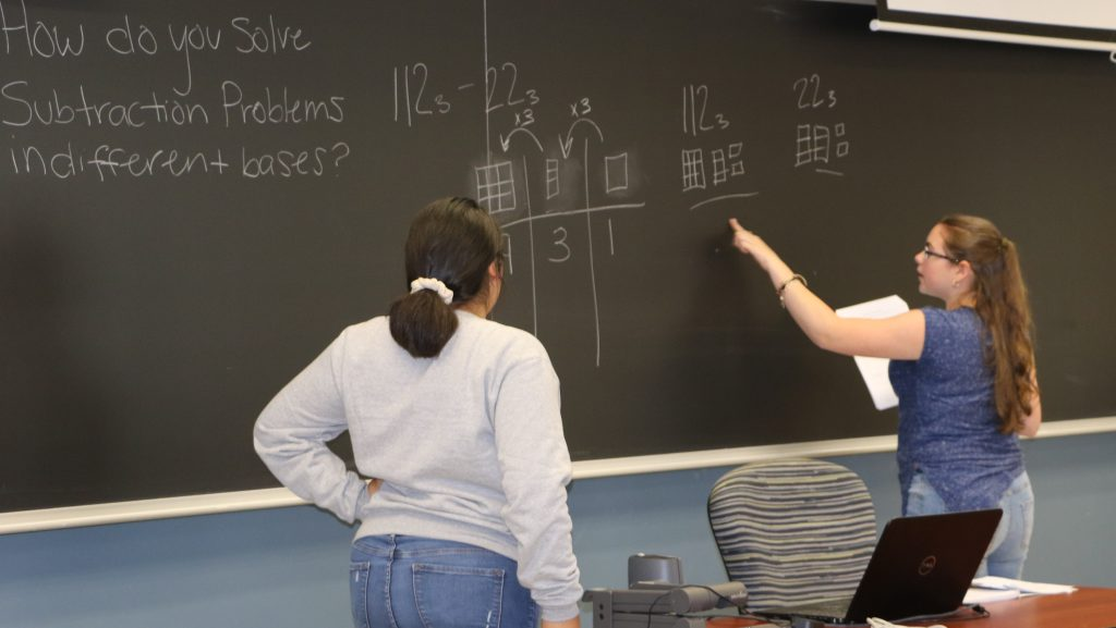 Teachers of Tomorrow Pipeline students solve math problem on chalkboard