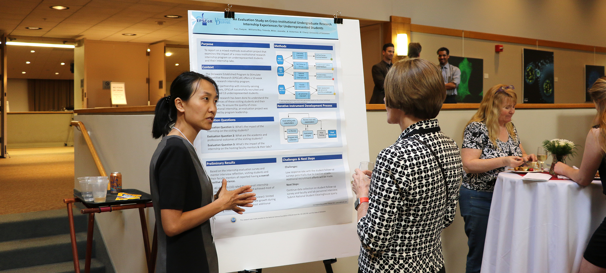 Dean Carol Vukelich reviews a research poster at the Steele Symposium