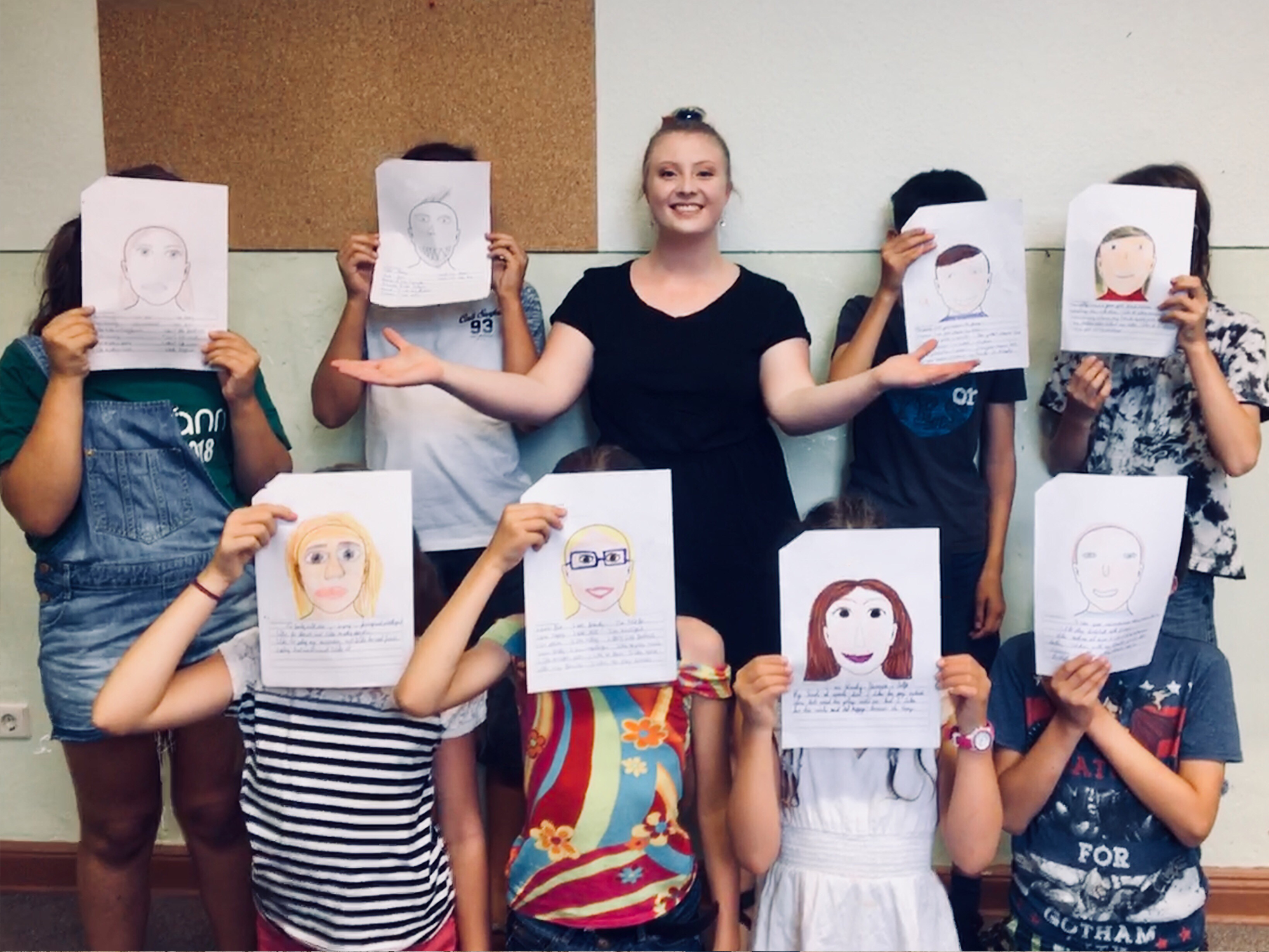 Erica Komp poses with German students who are holding their self portrait drawings
