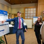 Student discusses research poster with faculty at 2019 Steele Symposium
