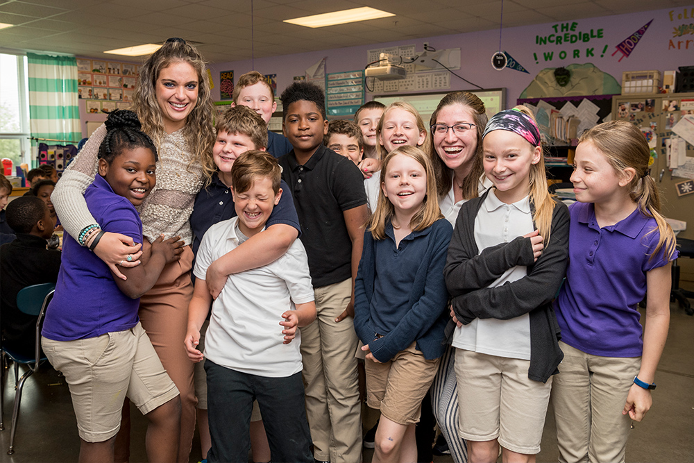Two students teachers hug children in classroom