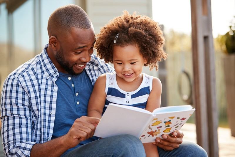 A father reads to his daughter.