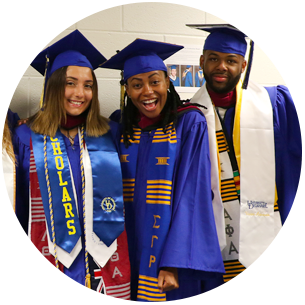 Three smiling students at the CEHD commencement ceremony