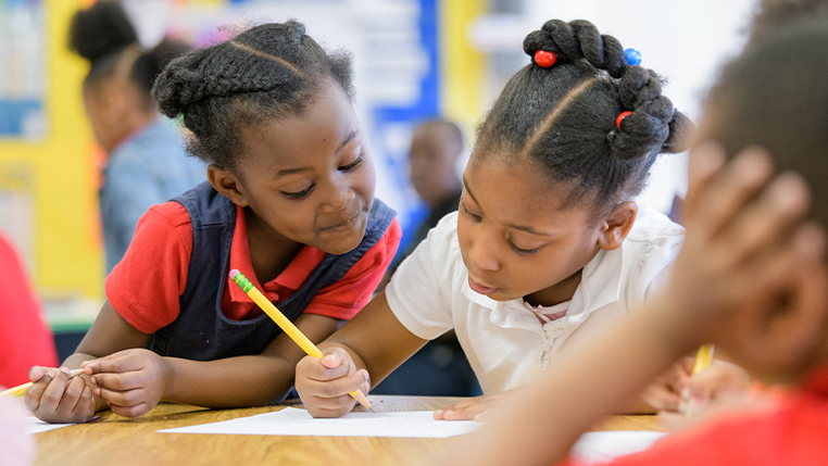 Two black female students working on an assignment in class
