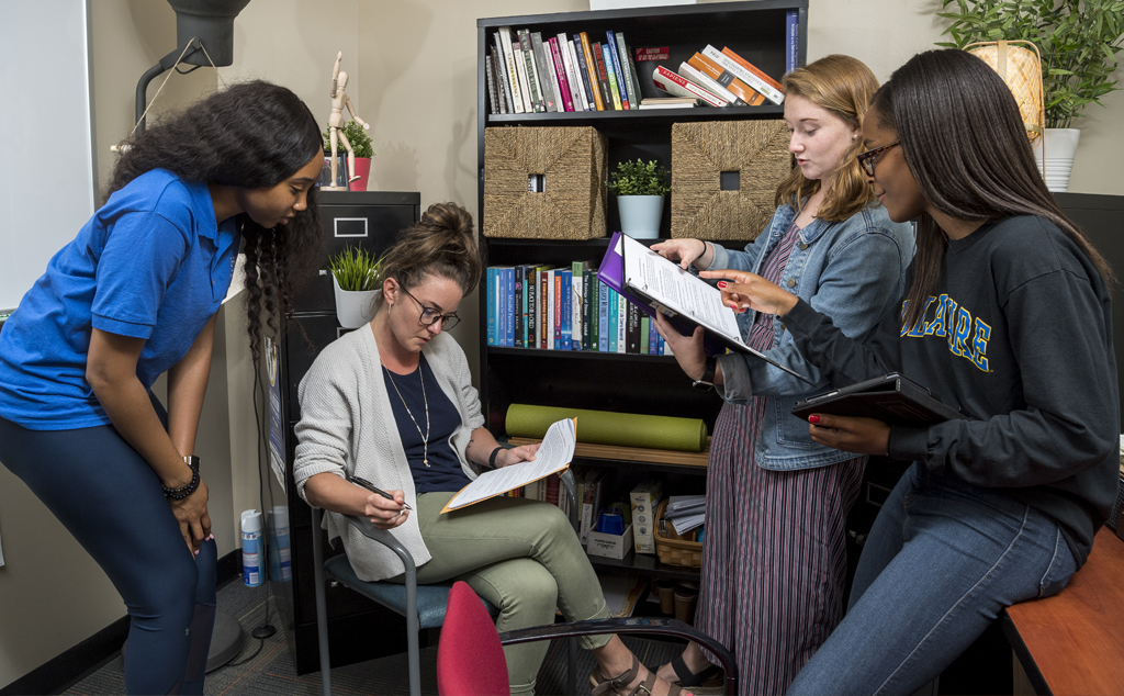 Summer Research students Khadi Jackson (royal blue shirt) and Colleen Mueller (jean jacket) are doing research Recovery Residences Effectiveness along with graduate students Jhane Campbell (black sweatshirt) and Ginnie Sawyer Morris (light blue shirt).