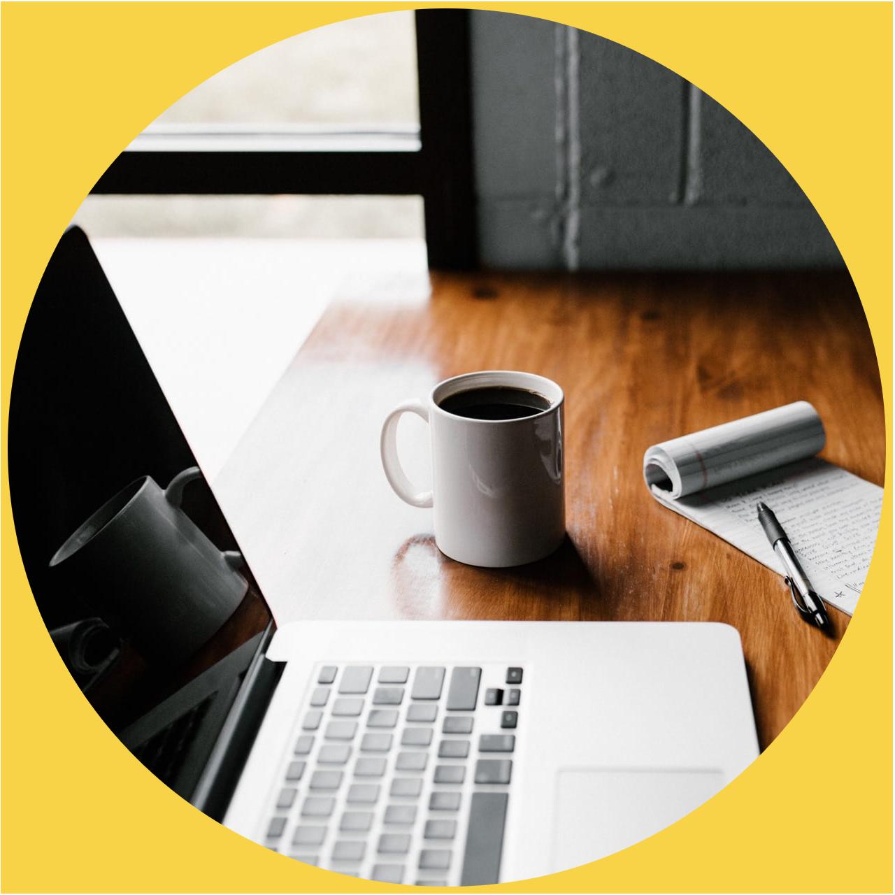 Mug, laptop, and notebook on a desk