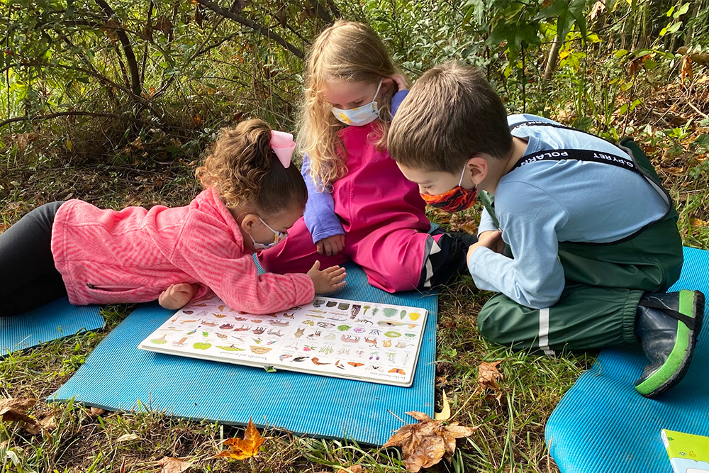 Three children reading a book outside at the UD Lab School