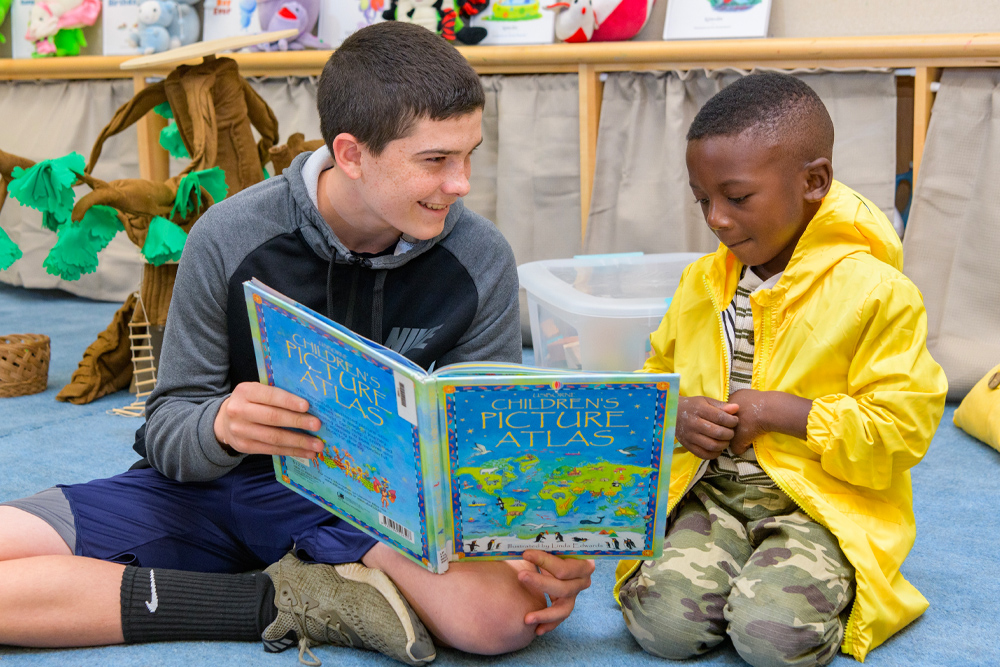 Undergraduate student reading to child at The College School