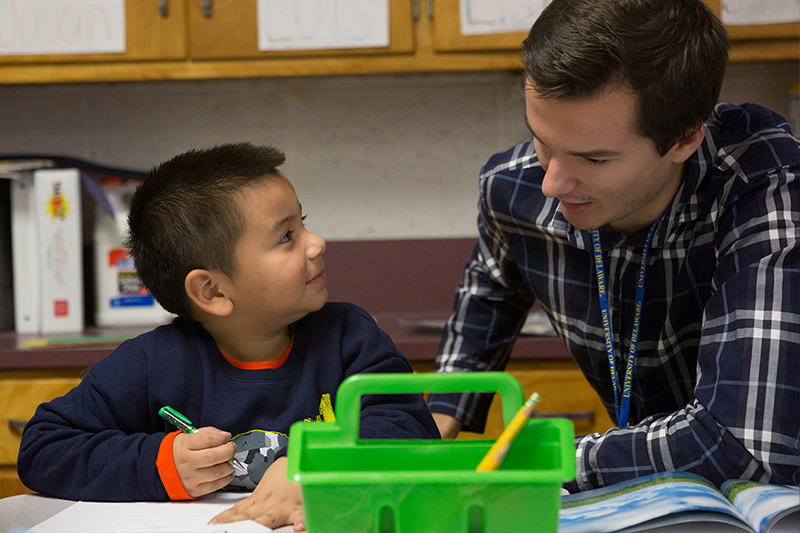 Student helping child with assignment in classroom